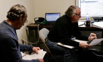 Bethel City Manager Peter Williams, left, and then-Finance Director Jim Chevigny review the FY 2018 budget at Bethel City Hall on June 8, 2017. Chevigny resigned Wednesday, June 27, 2018. (Photo by Christine Trudeau/KYUK)