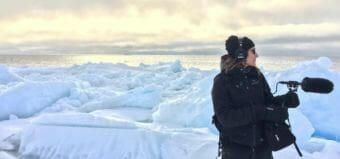 Ravenna Koenig of Alaska's Energy Desk/KTOO stands on the lead edge of the sea ice while recording sound for a story about Arctic Field School. (Photo courtesy of Lindsay Cameron)