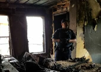A Juneau Police Department officer stands in the burned third-floor bedroom where the fire that damaged the Dapcevich House began. (Photo courtesy of Ernestine Hayes)