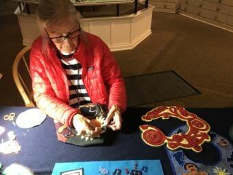 Chloe French adds beads to her felt bib. (Photo by Rachel Cassandra/KCAW)