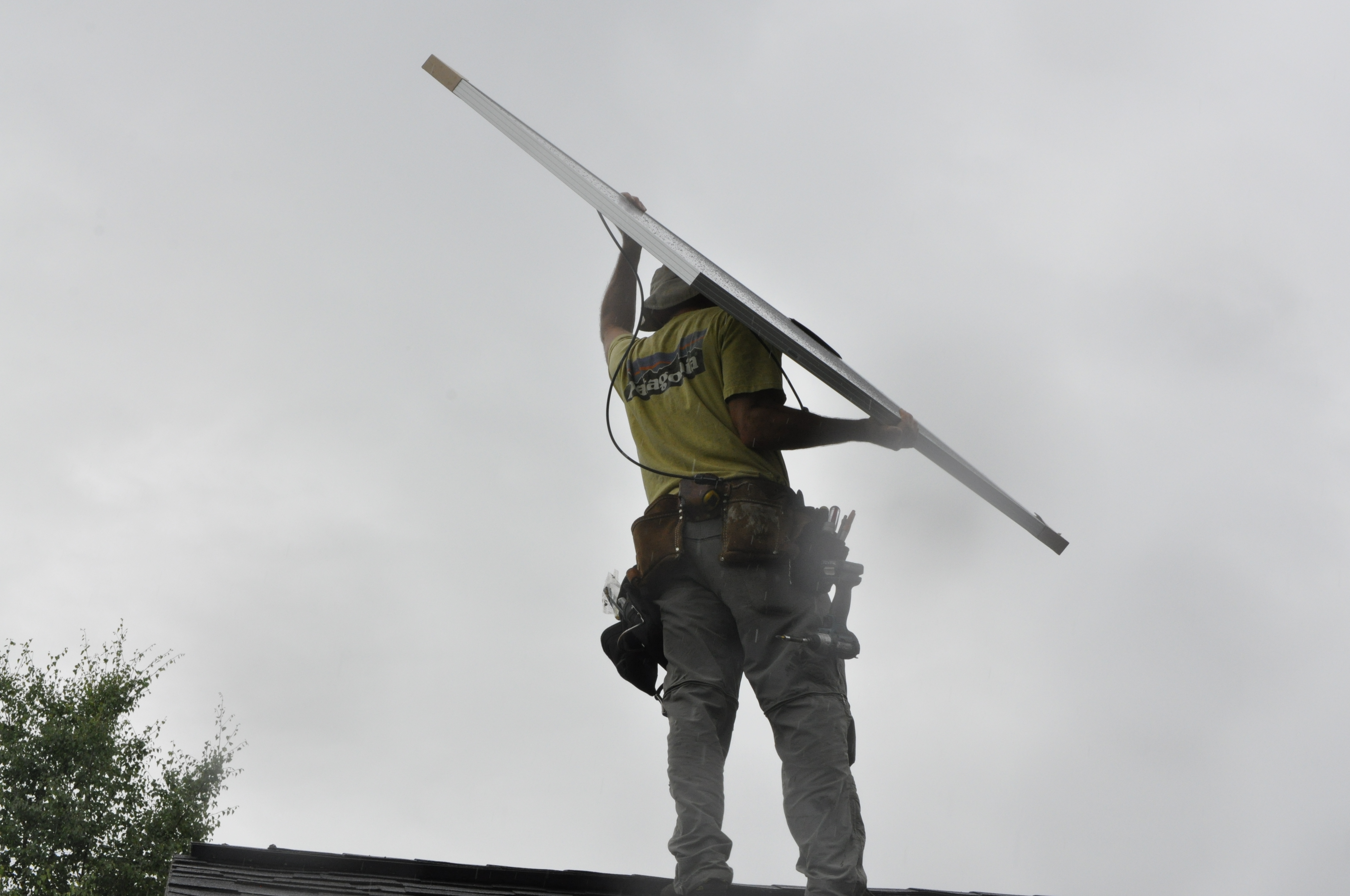 Anchorage Solar employee Tim Remick hoists a solar panel over his head before installing it on Solarize Anchorage participant Lisa Pekar's roof. The program saved participants around 10 percent on solar panel installations. (Photo by Erin McKinstry, Alaska Public Media)