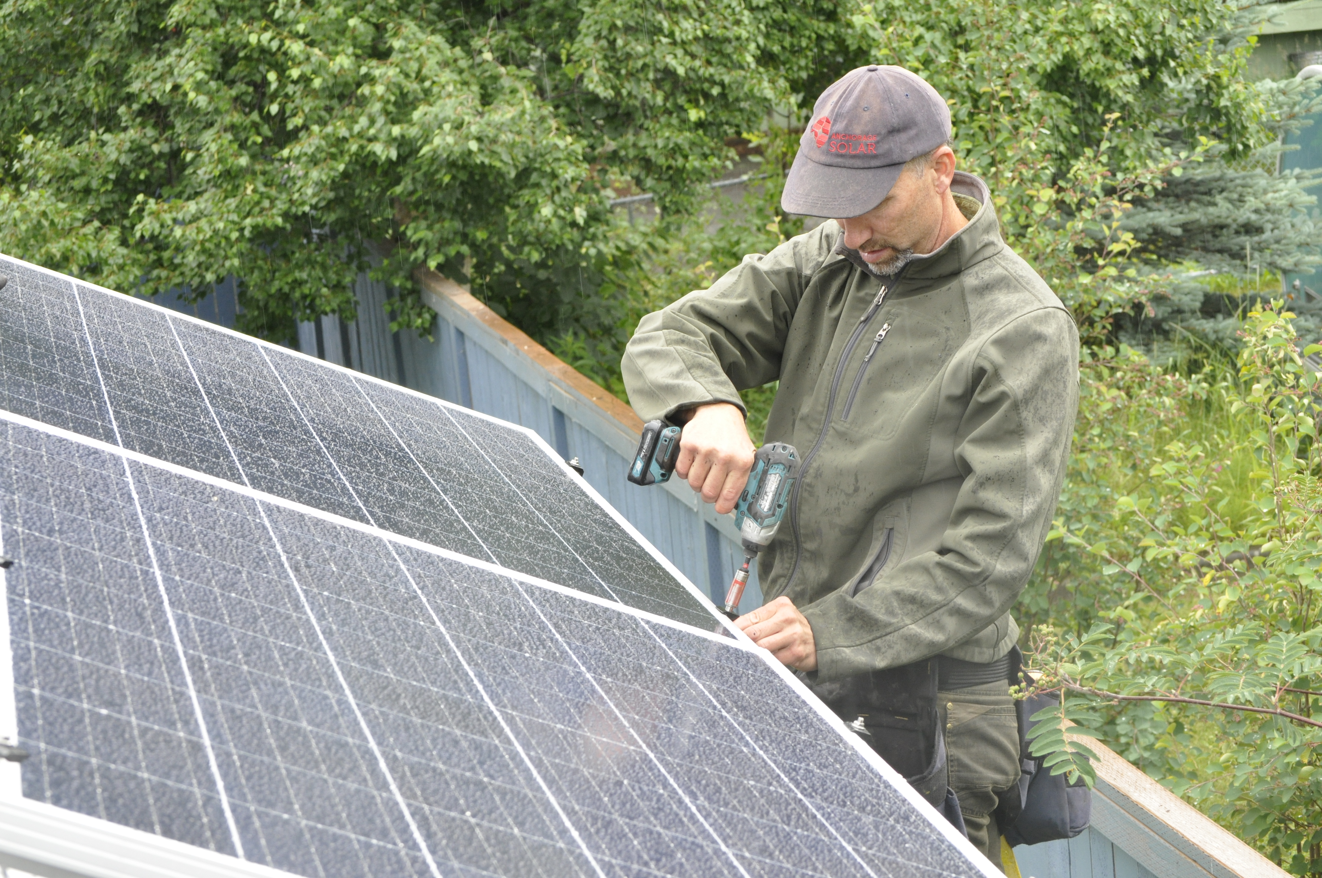 """Anchorage Solar owner Ben May secures a solar panel on Lisa Pekar's garage roof. He said business has increased almost eight-fold since he opened in 2016. """"You caught me mid-way through a costume change,"""" he said. """"I wear many hats."""" (Photo by Erin McKinstry/Alaska Public Media)"""