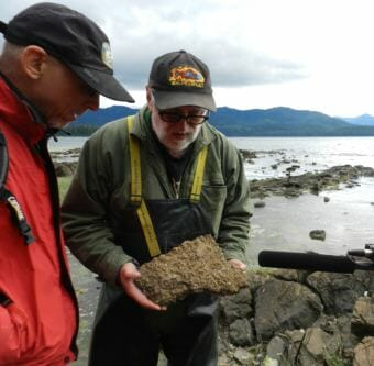 Dave Strassman, left, and Ray Troll investigate a block of limestone crusted with fossil shells. (Photo courtesy Josef Quitsland)