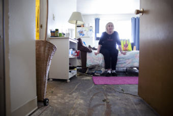 Terry Baker sits on her bed in an apartment recently stripped of wet carpet on July 12, 2018, at the Mendenhall Tower apartments in Juneau. Baker's apartment is near one that caught fire and damaged the building extensively.