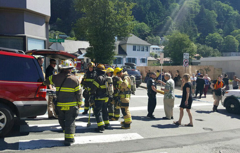 Firefighters and residents outside Mendenhall Tower Apartments the morning of July 5, 2018, after some residents were evacuated after a fire. (Photo by Tripp J Crouse/KTOO)