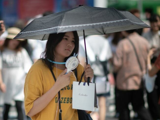 A woman uses a portable fan to cool herself in Tokyo on Tuesday as Japan suffers from a heat wave. Scientists say extreme weather events will likely happen more often as the planet gets warmer. (Photo by Martin Bureau/AFP/Getty Images)