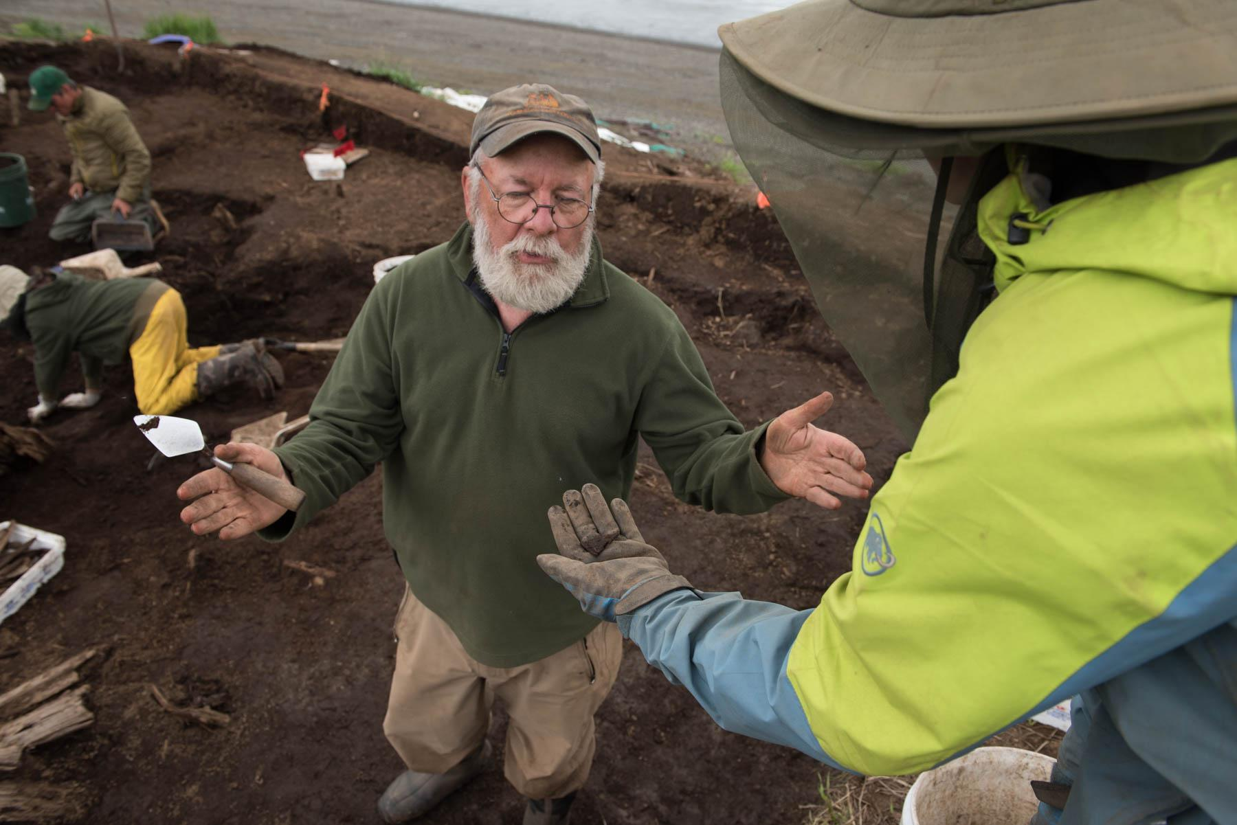 Dr. Rick Knecht explains July 24, 2018, the purpose of a small triangular piece of leather to student Lauren Phillips while digging at the Nunalleq site . The leather is likely caribou hide and was used to patch a larger piece of hide or clothing. (Photo by Katie Basile/KYUK)