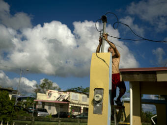In October 2017, a resident tries to connect electrical lines downed by Hurricane Maria in Toa Baja. Puerto Rican officials say electricity has returned to all residents without it after the hurricane. (Photo by Ramon Espinosa/Associated Press)