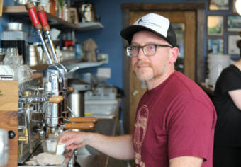 Austin Schwartz, with a short beard, glasses and a baseball cap, holds a cup of coffee under the nozzle of an espresso machine