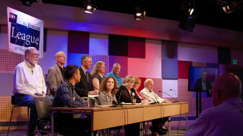 Juneau Assembly candidates on stage and a live audience @360 watch District 2 candidate Garrett Schoenberger's pre-recorded statement at the Juneau League of Women Voters Municipal Candidates Forum on Sept. 20, 2018. Back row from left to right: Loren Jones, Wade Bryson, Don Habeger, Michelle Bonnet Hale, Emil Mackey. Front row: Norton Gregory, Saralyn Tabachnick, Beth Weldon, Carole Triem and Tom Williams.