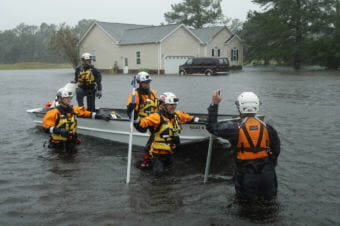 Members of the FEMA Urban Search and Rescue Task Force 4 search a flooded neighborhood for people who may have been trapped by the rising floodwaters during now-tropical storm Florence in North Carolina.