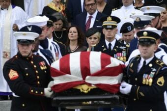 The casket of Sen. John McCain, R-Arizona., is carried out of the Washington National Cathedral in Washington, Saturday, Sept. 1, 2018, after a memorial service, as Cindy McCain is escorted by her son Jimmy McCain and other family members.