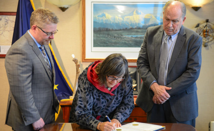 Valerie Nurr'araaluk Davidson signs paperwork as part of a swearing in ceremony with Gov. Bill Walker, right, and Chief of Staff Scott Kendall in Anchorage on Tuesday, Oct. 16, 2018.