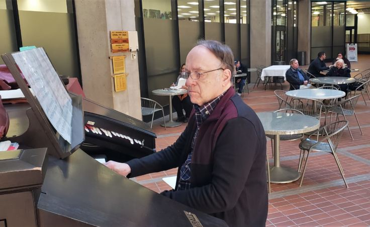 J. Allan MacKinnon plays Kimball organ in the atrium of the State Office Building in Juneau on Friday, Oct. 26, 2018. He's one of a handful of organ players in town who regularly play Friday lunchtime concerts on it.