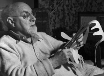 Henri Matisse works on a paper cut out in this undated photo.