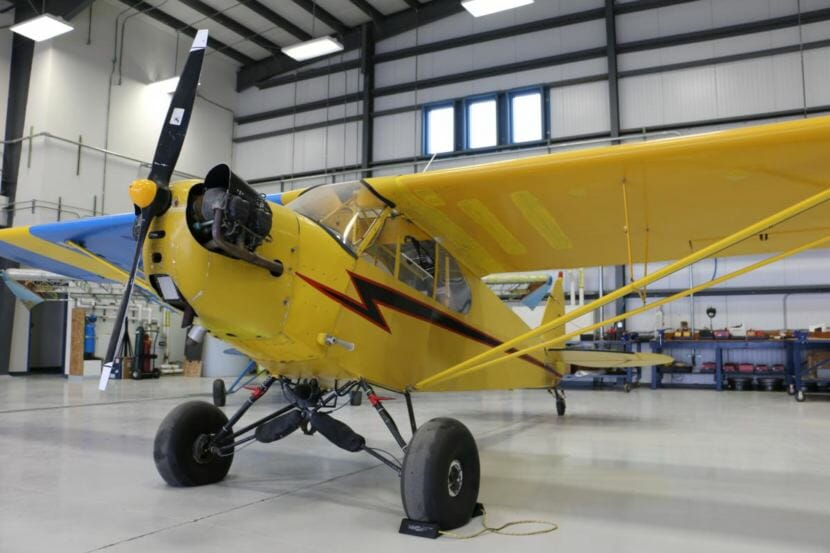 Yellow airplane in a hangar.