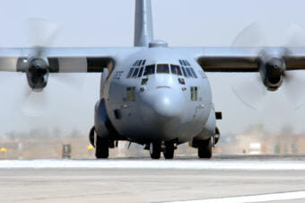 A C-130 Hercules taxis on a runway.