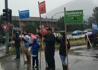 Supporters of Mike Dunleavy's campaign for governor wave campaign signs on the Aug. 21 primary in Juneau. The group Dunleavy for Alaska, the American Civil Liberties Union of Alaska and Eric Seibles sued over state enforcement of a ban on outdoor advertising in July. A judge issued a temporary restraining order on Monday allowing some political signs. (Photo by Andrew Kitchenman/KTOO)