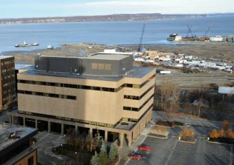 View looking northwesterly from the Hotel Captain Cook in Anchorage, Alaska. At left is the Boney Courthouse, the older of the two state courthouses in Anchorage, which houses the law library, magistrate courts and the chambers of the Alaska Supreme Court. The mouth of Ship Creek, Knik Arm and Point MacKenzie can be seen in the background.