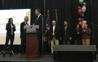 Gov. Mike Dunleavy (center) was surrounded by his family at his inaugural celebration at the Menard Sports Center in Wasilla. From left: his daughter Ceil Ann; his brother Francis, of Houston, Texas, and Salt Lake City, Utah; Mike Dunleavy; his brother William, of Allentown, Pennsylvania; his brother Patrick of Scranton, Pennsylvania; his daughter Catherine; and his daughter Maggie. His wife Rose is obscured in the photo. Dec. 4, 2018. (Photo by Andrew Kitchenman/KTOO and Alaska Public Media)