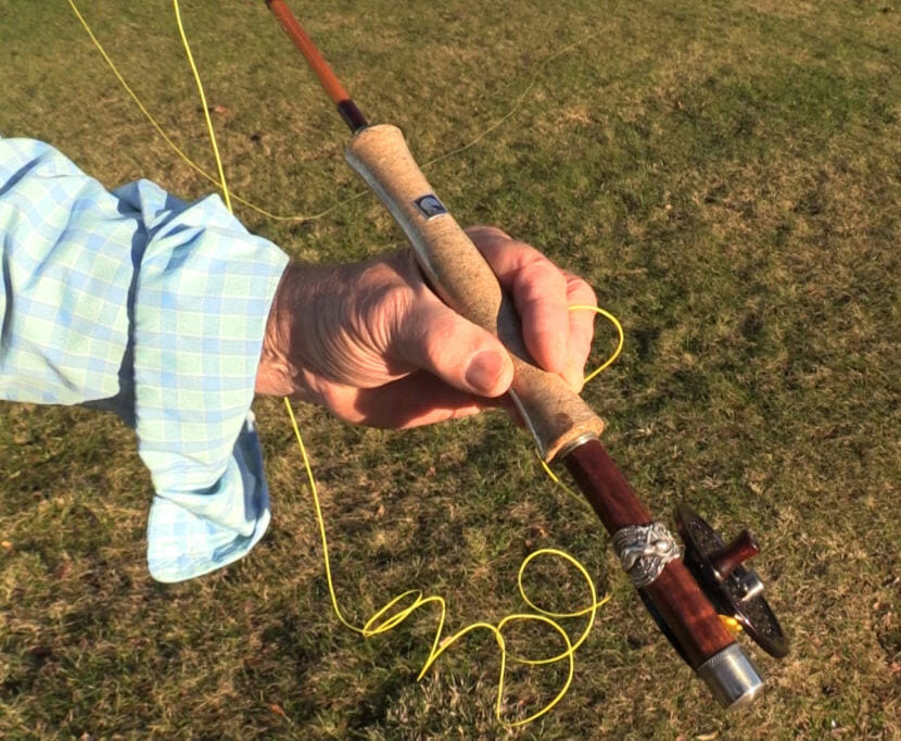 A silver spoon with the image of goddess Minerva on a Hawaiian background serves as a reel cup on one of Jon Lyman's handcrafted bamboo fly rods.