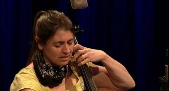 A picture of a woman with a bandana on playing cello in a tv studio. Still image of Kat Moore of the Forest That Never Sleeps performing a Red Carpet Concert at KTOO Public Media in April 2018.