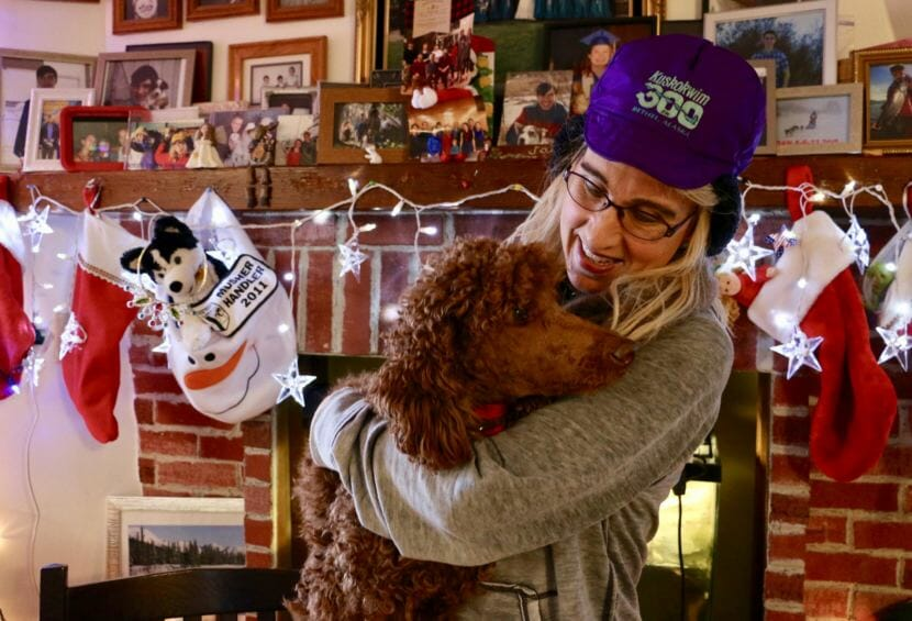 Jackie Klejka wears her signature K300 hat while holding her indoor dog Jersey inside her Bethel home, which is heavily decorated with sled dog paraphernalia. Klejka has been coordinating the K300 veterinary program since 1993. (Photo by Anna Rose MacArthur/KYUK)