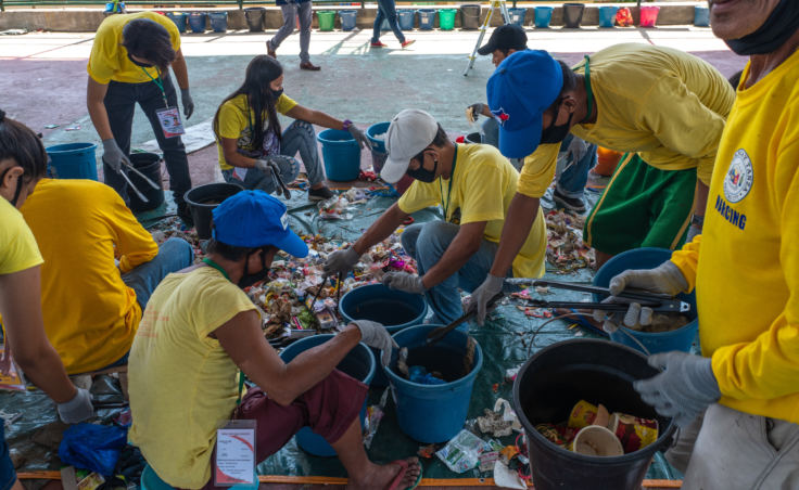 Volunteers sort trash items in a brand audit of plastic waste in Navotas, Manila. They keep track of the brands they find and publish results on the Web. Their goal is to pressure companies to change their plastic packaging.