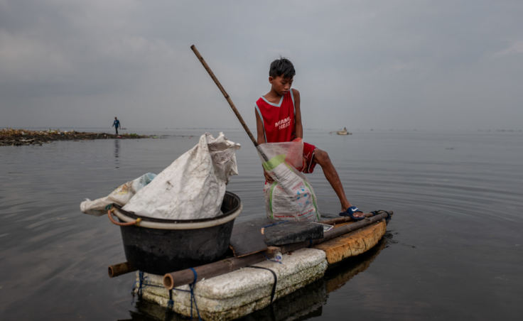 Children fill sacks with plastic trash from Manila Bay that they intend to sell to recyclers. (Photo by Jes Aznar for NPR)