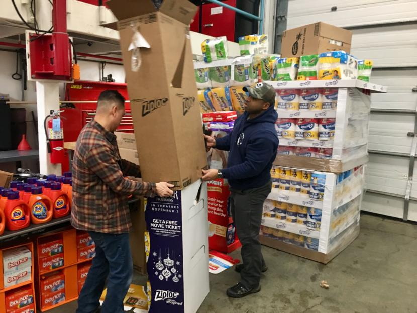 Quy Nguyen (left) and Mahire A'Giza unpack donations at the consumables pantry on Jan. 22, 2019. (Photo by Zoe Grueskin/KTOO)