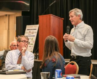 Juneau City Manager Rorie Watt looks on as CLIAA President John Binkley speaks at the Southeast Conference Mid-Session Summit in Juneau on Feb. 13, 2019. (Photo by Heather Holt/Southeast Conference)