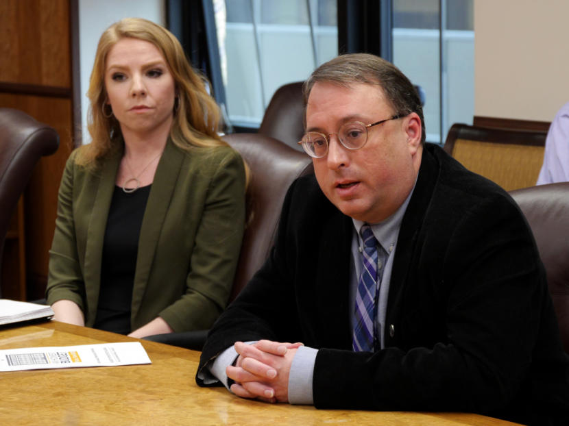 Policy Director Mike Barnhill of the Office of Management and Budget answers a reporter's question about the most recent version of Gov. Michael Dunleavy's state operating budget in the governor's cabinet room in the Capitol in Juneau on Feb. 13, 2019. OMB Deputy Director Laura Cramer, is seated next to him. They were at a budget briefing held for the press.
