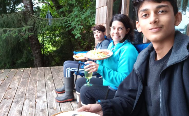 """Zain Mufti (right) eating with his host family. Mufti says his family at home in Pakistan are confused by his Alaskan diet, which contains less meat. He says he tells them, """"There's a whole world beyond meat -- there's cheese!"""" (Photo used with permission)"""