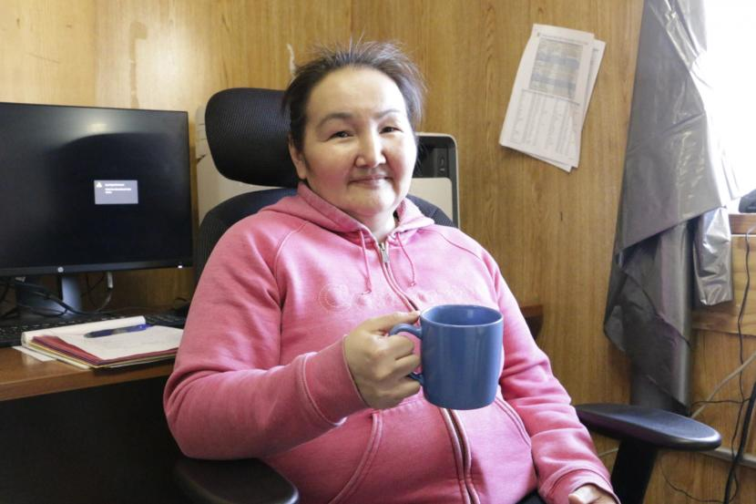 Eek Tribal Administrator and city council member Stella Alexie drinks coffee made with rain water in the Eek tribal/city office building. Many residents prefer to brew coffee and tea with rain water, saying it tastes better without chlorine on Feb. 21, 2019. (Photo by Anna Rose MacArthur/KYUK)