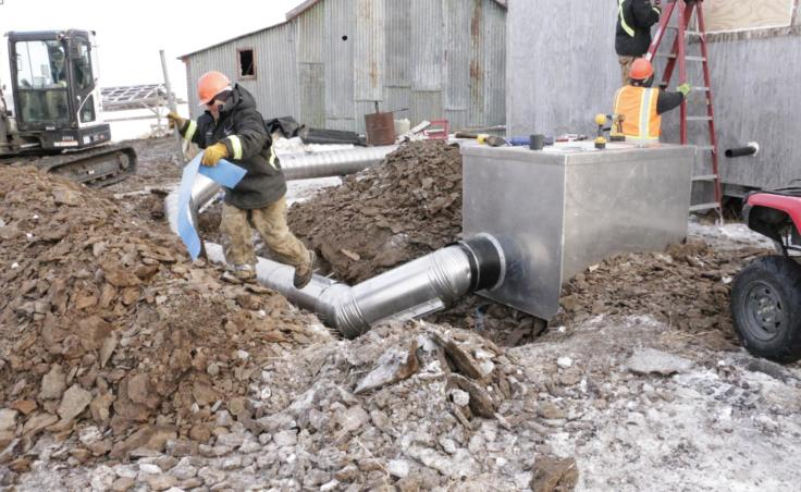ANTHC workers install a water and sewer system to an Eek home on February 21, 2019. (Photo by Anna Rose MacArthur/KYUK)
