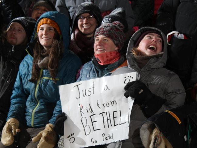 Mushing fans from Bethel (left to right) Ashley Fairbanks Glasheen, Rachel DeHaan, and Madelene Reichard cheer Pete Kaiser on in Nome as he wins the Iditarod Race on March 13, 2019. (Photo by Zachariah Hughes/APRN)