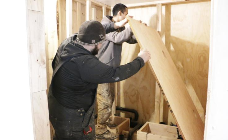 For many Eek homes, installing plumbing means building a bathroom in the house. Plumbers Nicholas Henry and Robert Sitton are pictured here on February 20, 2019. (Photo by Anna Rose MacArthur/KYUK)