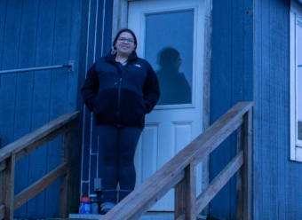 Serafima Edelen stands in front of her house on St. Paul island in January, 2019.