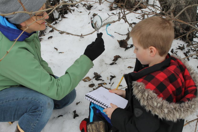 Justina Hotch helps a student examine a bud. (Photo by Henry Leasia/KHNS)