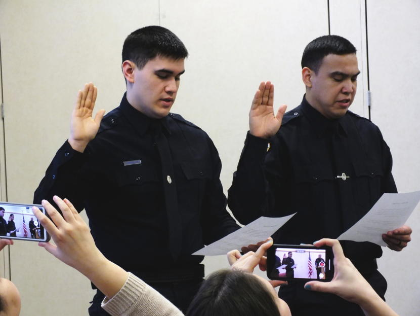 Family and friends record the swearing in of new Juneau Police Officers Jonah Hennings-Booth and Duain White during a ceremony at the Juneau Police Department Feb. 21, 2019.