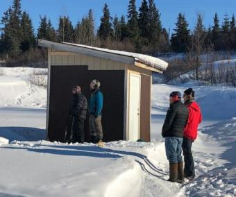 Men wait their turn to shoot at the Kachemak Gun Club and Range.