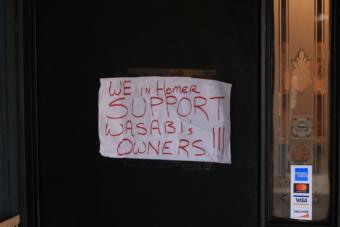 The same day racial slurs were spray-painted on the front of the restaurant, a sign from supporters was placed on the front door. (Photo by Aaron Bolton/KBBI)