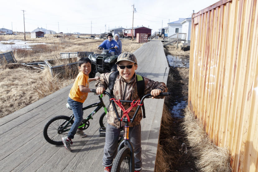 Kids play on the boardwalk that snakes through town on Wednesday, April 3, in Tuntutuliak, Alaska. (Photo by Rashah McChesney)
