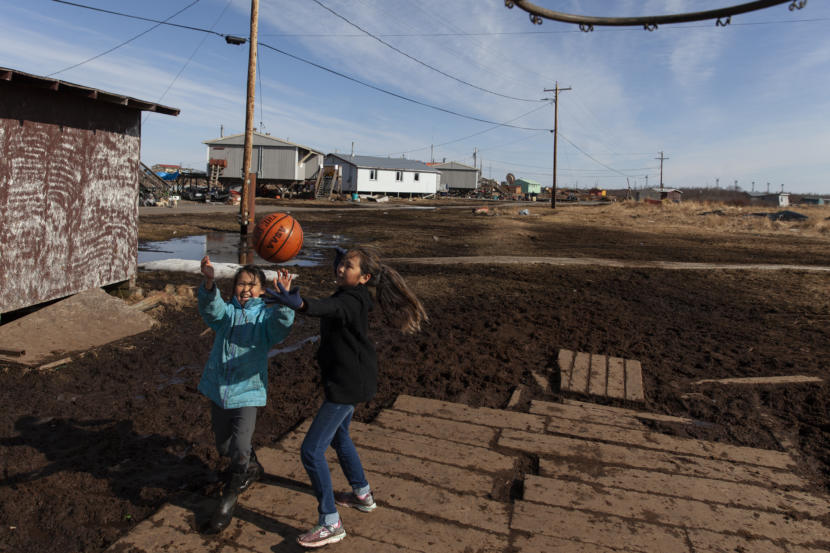 Megan Evan, 10, and Christine Aguchak, 9, play basketball after school on Wednesday, April 3, in Tuntutuliak, Alaska. (Photo by Rashah McChesney/Alaska's Energy Desk)