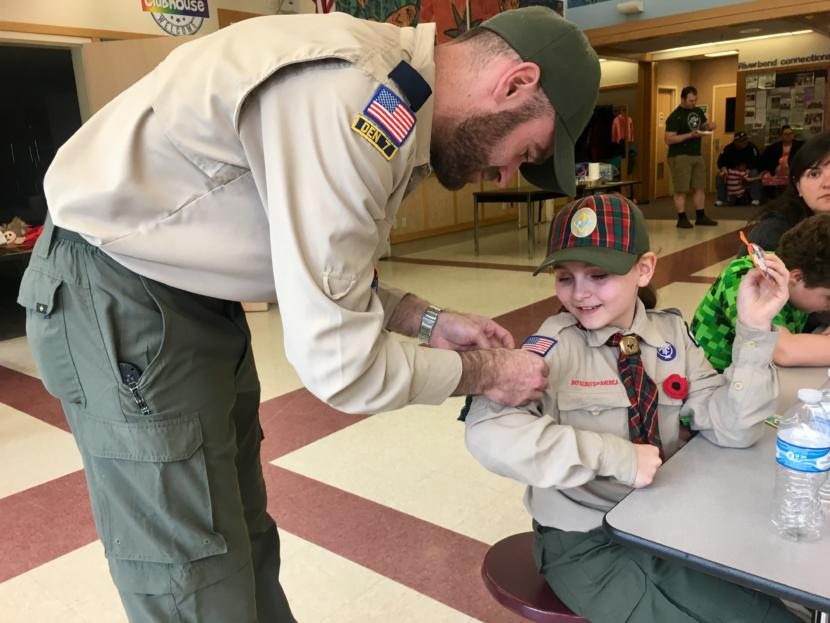 Kelsie Powers' father -- and assistant den leader -- attaches the new badges she earned to her Scout uniform at a pack meeting on April 20, 2019. (Photo by Zoe Grueskin/KTOO)