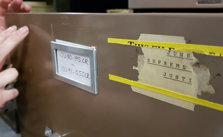 A filing cabinet label indicates criminal cases from 1980 and 1991 are in the drawer in a tertiary, basement file storage area of the Dimond Courthouse in Juneau on April 22, 2019. The court retains the physical files of cases with an unresolved element, such as a probation period or potential appeal.