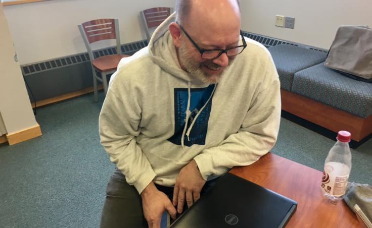 """Volunteer mentor Kerry Lear at a Thunder Mountain High School robotics practice on April 9, 2019. Lear says he helps the teams with troubleshooting. He advises them to change one thing at a time: """"Don't tear everything apart. Just tear one thing apart."""" (Photo by Zoe Grueskin/KTOO)"""