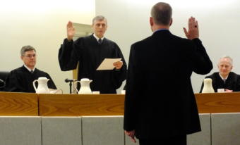 Senior Superior Court Judge Donald Hopwood administers the oath of office to Juneau Superior Court Judge Daniel Schally during his installation ceremony March 29, 2019 at the Dimond Courthouse. Alaska Supreme Court Chief Justice Joel Bolger (left) and Juneau Superior Court Judge Philip Pallenberg (right) look on.