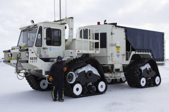 A worker stands in front of a vibe truck being used as part of BP's 3-D seismic program at Prudhoe Bay this winter.