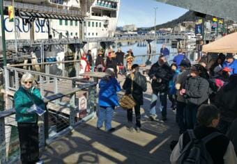 Vicki Logan of Travel Juneau greets and hands out walking maps to passengers of the Ruby Princess at the Franklin Dock on Sunday, April 28, 2019. The Yées Ḵu.Oo dance group performs behind her as part of a welcome party for the first big cruise ship of the season.